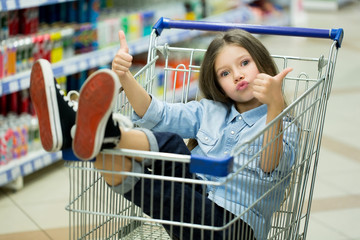 A little girl rides a cart in a supermarket and shows her finger up.