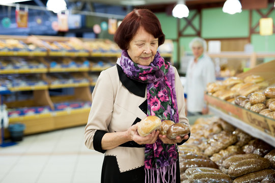 Woman during shopping bread and baguette at supermarket store shop