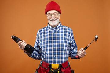 Repair, renovation, construction and occupation concept. Picture of emotional funny unshaven elderly carpenter or plumber going to fix something, laughing happily, holding drill and hammer
