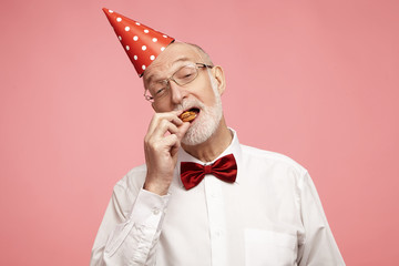 Horizontal image of attractive stylish senior male with gray beard and cone hat on his head eating birthday cake, placing last piece in his mouth with joyful facial expression, teasing you