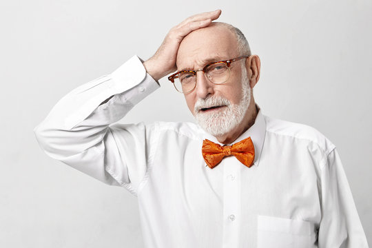Depressed elderly 65 year old businessman with thick gray beard having frustrated unhappy painful facial expression, holding hand on his bald head, stressed because his business company ruined