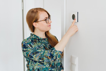 Young woman checking a wall thermostat