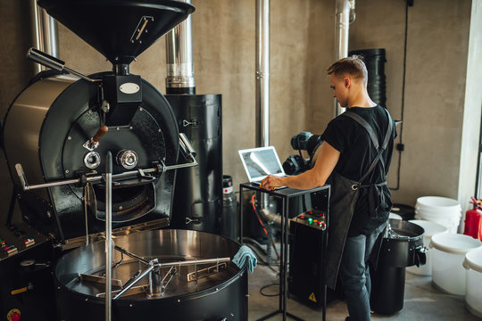 Young man coffee roaster working in roastery, coffee roasting in specialty coffee roastery.