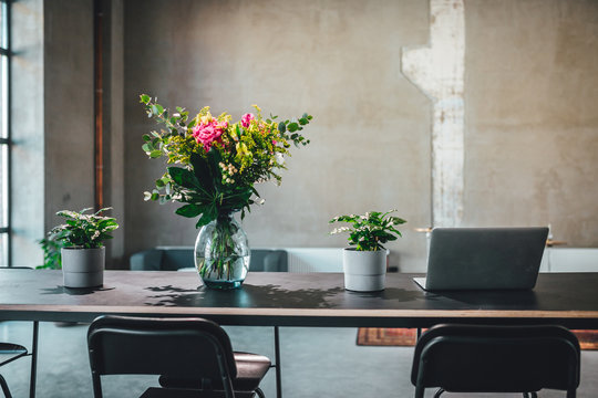 Working table with flowers and laptop in industrial environment