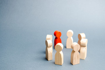 People stand in a circle on a gray background. Communication. Business team, teamwork, team spirit. Wooden figures of people. A circle of people. discussion, cooperation, cooperation. Selective focus