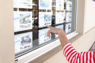 woman hand looks at the window of a real estate agency in the street