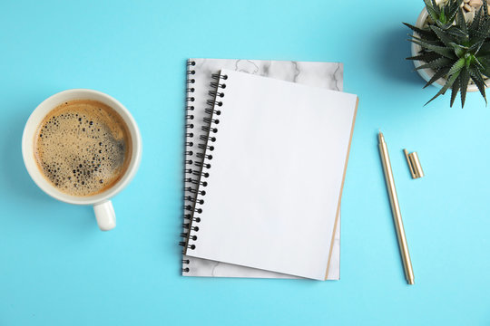 Flat lay composition with notebooks and coffee on color background