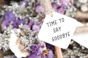 Time to say goodbye word on card and purple flower background.