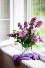 Photo sur Plexiglas Lilac Spring tender bouquet of beautiful lilac in glass vase near window in daylight