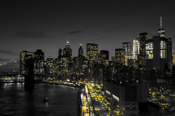 New York City black and white night skyline with golden yellow lights glowing in downtown Manhattan
