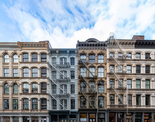 Exterior view of old apartment buildings in the SoHo neighborhood of Manhattan in New York City with empty blue sky