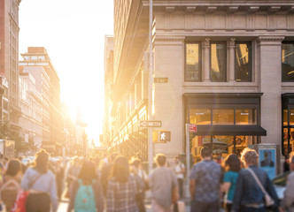 Crowd of anonymous people walking down the busy sidewalk on 23rd Street in Manhattan, New York City with bright light of sunset