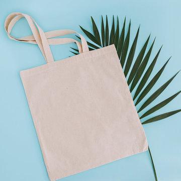 White cotton bag and palm leaf on blue background. Mock up for design.