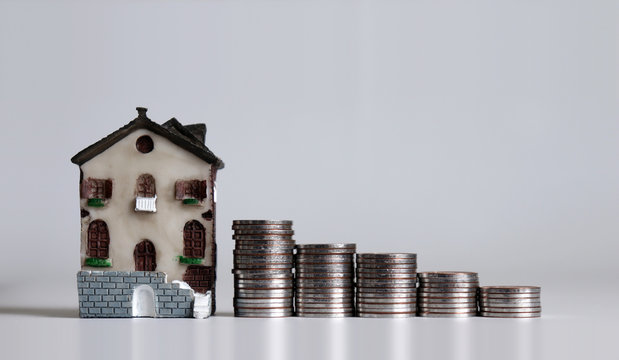 Miniature house and pile of coins in the shape of a graph.