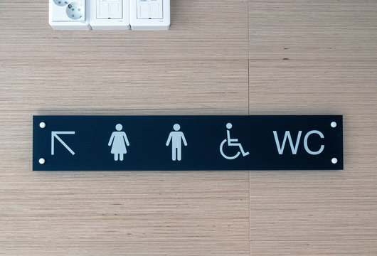 Toilet sign and direction on wall