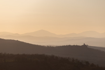 Beautiful view of Tuscany hills at sunset, with mist and warm colors