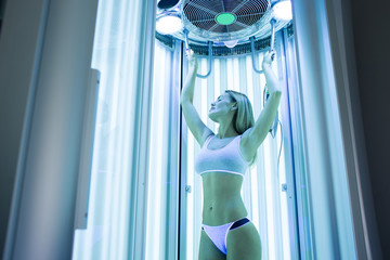 Close-up of a cute elegant girl enjoying a tan in a modern solarium. Portrait of a healthy young woman in a solarium, she holds her hands up and closes her eyes with pleasure