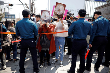 Pro-abortion law protesters hold up a picture depicting fetuses in sight of anti-abortion law protesters during a rally to support the abortion law in front of the constitutional court in Seoul