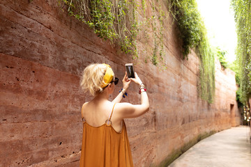 Back view of a woman traveler standing at park and taking a photo with her smartphone camera.