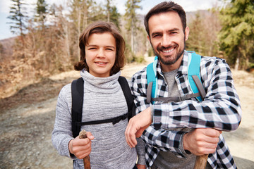 Portrait of dad and his son with backpacks in the forest