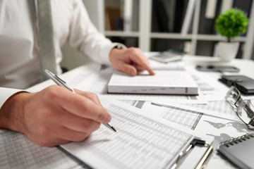 Obraz Businessman working at office and calculating finance, reads and writes reports. Business financial accounting concept. - fototapety do salonu