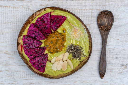 Green avocado smoothie in coconut bowl with dragon fruit, passion fruit, almond flakes, coconut chips and chia seeds for breakfast , close up. The concept of healthy eating, superfood