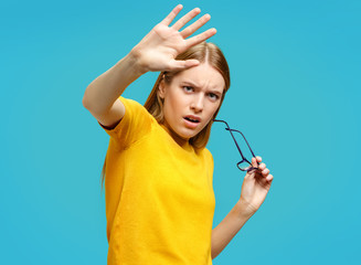 Scared girl outstretched her palm, hiding her face. Photo of attractive girl in yellow sweater on blue background. Emotions and feelings concept.