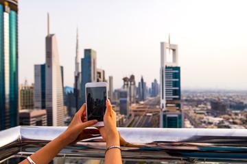 Woman taking photo of Dubai cityscape