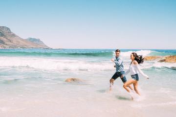 Junges Paar voller Liebe, Freude und Freiheit am Strand im sonnigen Kapstadt