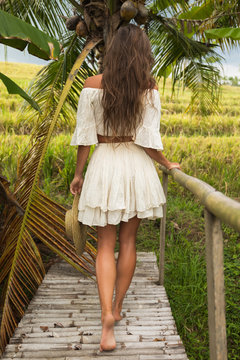 Woman walking by old wooden bridge in the countryside