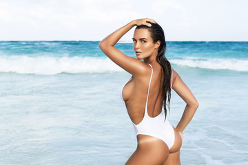 Sexy woman wearing white swimsuit is posing on the beach