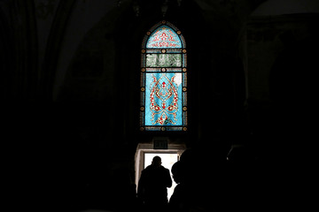 Visitors are silhouetted as they walk below a stained glass window in the Cenacle, a hall revered by Christians as the site of Jesus' Last Supper, in Mount Zion near Jerusalem's Old City