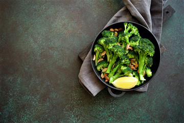 Broccoli with lemon and almond in a frying pan. Nutrition concept