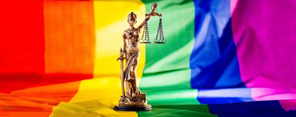 Statue of justice symbol of law and justice with lgbt flag