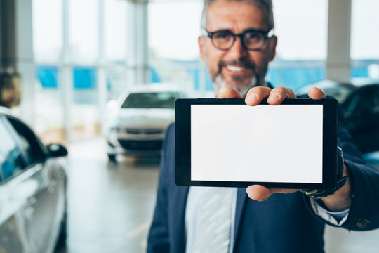 senior businessman holding tablet with blank screen in car showroom