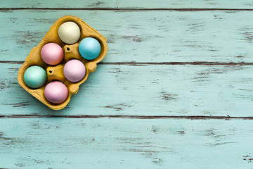 Top view of colored Easter eggs of sugar on delicate wooden background