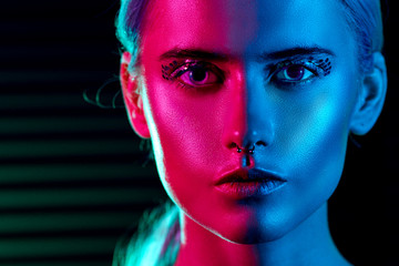 Fashion model blonde woman in colorful bright neon lights posing in studio.