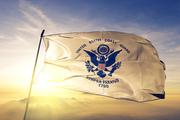 United States Coast Guard flag waving on the top sunrise mist fog Wall mural