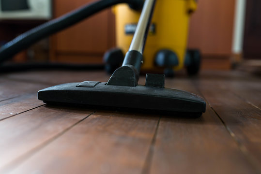 Industrial vacuum cleaner on dusty wooden floor close up, shallow depth of field, copy space.