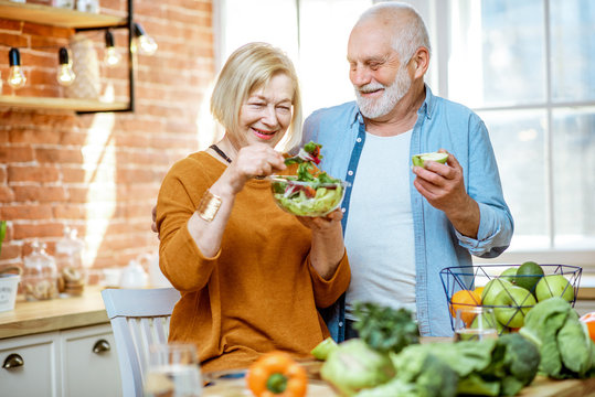 Portrait of a cheerful senior couple with salad and healthy food on the kitchen at home. Concept of healthy nutrition in older age