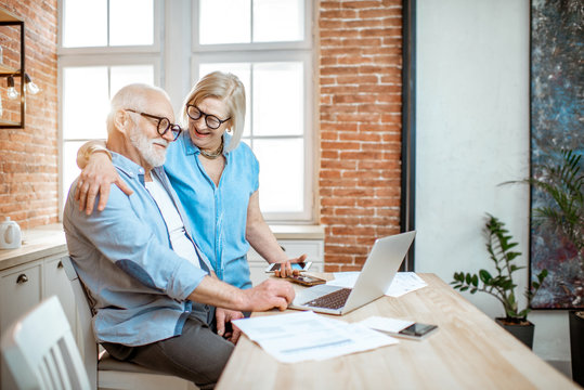 Beautiful senior couple in blue shirts hugging together working with laptop on the kitchen at home