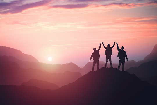 three guys celebrating victory on top of a mountain