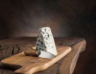 Wall Mural - Piece of blue cheese and cheese knife on the wooden board. Dark background.