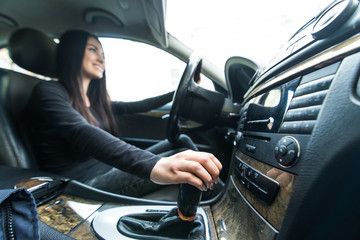 Young woman driver shifting the gear stick and driving a car