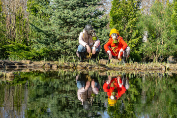 Fototapeta Take care of nature and save the planet for future generations. A little girl in red with sister squatting on bank of pond.. Heads of girls are hidden under gas masks. Say no to pollution.