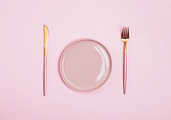 Pink plate, fork and knife isolated on pink background