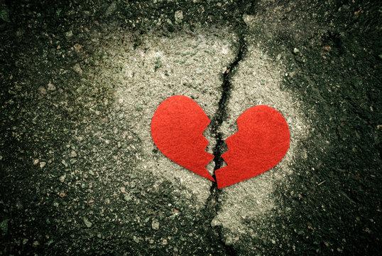 Broken red heart on cracked asphalt. divorce concept.
