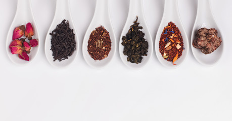 Wall Mural - Different variety of dry tea in white spoons on the white background