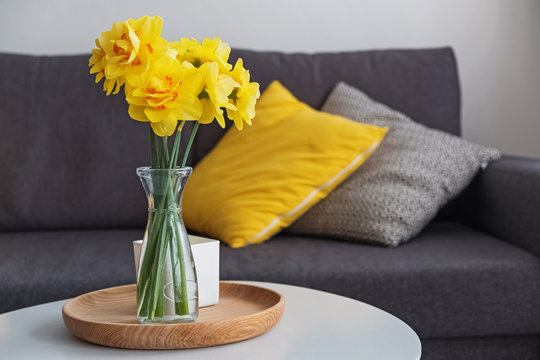 Yellow spring flowers in a vase standing in the living room on the coffe table
