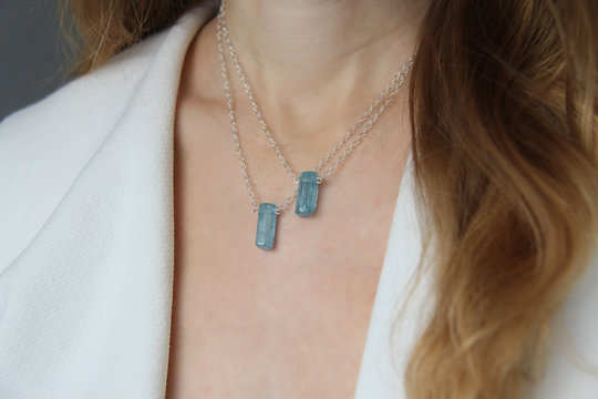 Crystal blue aquamarine beryl on a silver chain on the girl. Pendant aquamarine, pendant, decoration on the neck. Natural blue aquamarine. Minimalism, Zen. Copy space for your text